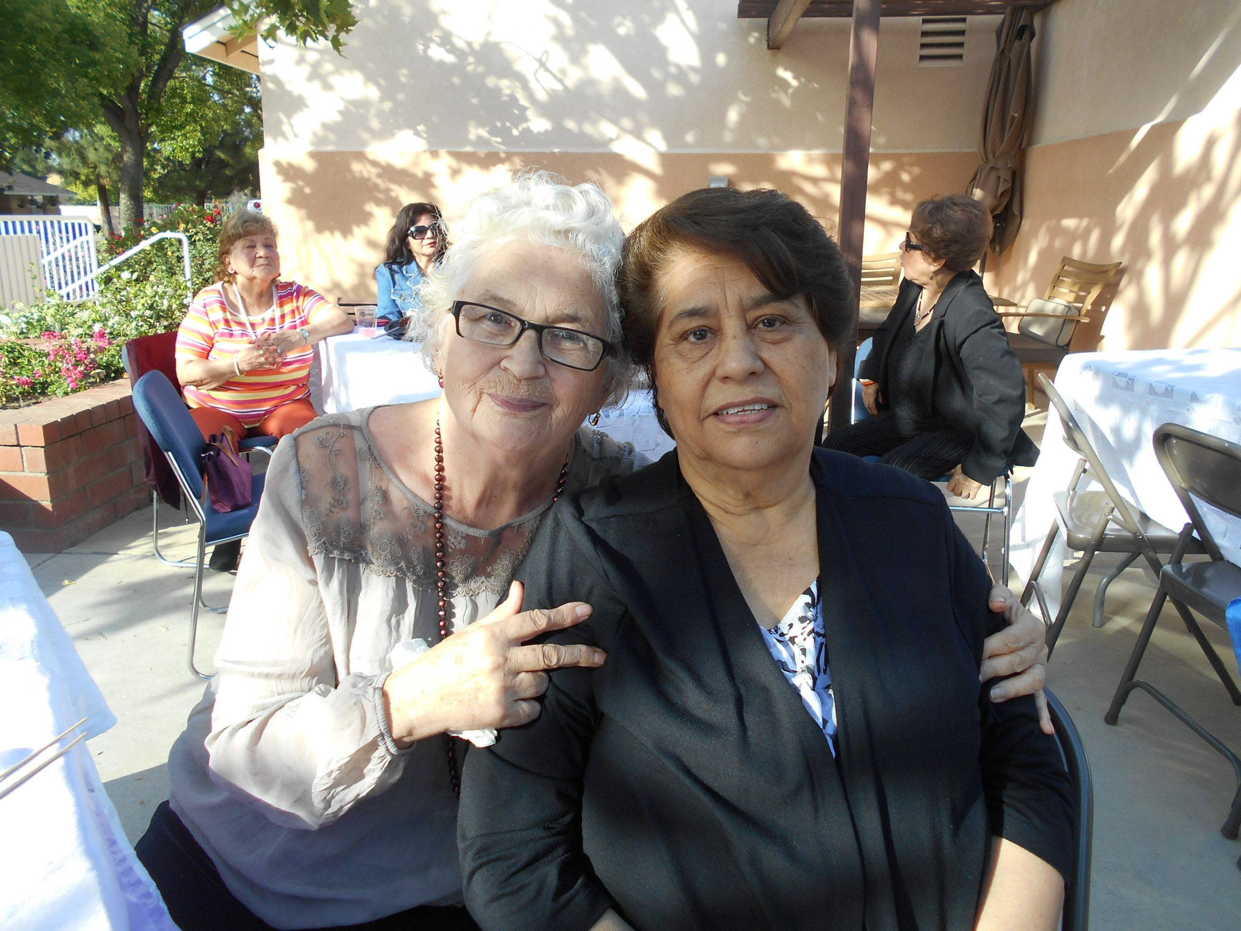 Two senior women, one with white hair and one with brown hair, sitting and posing for a picture at Cambridge Gardens senior housing community.