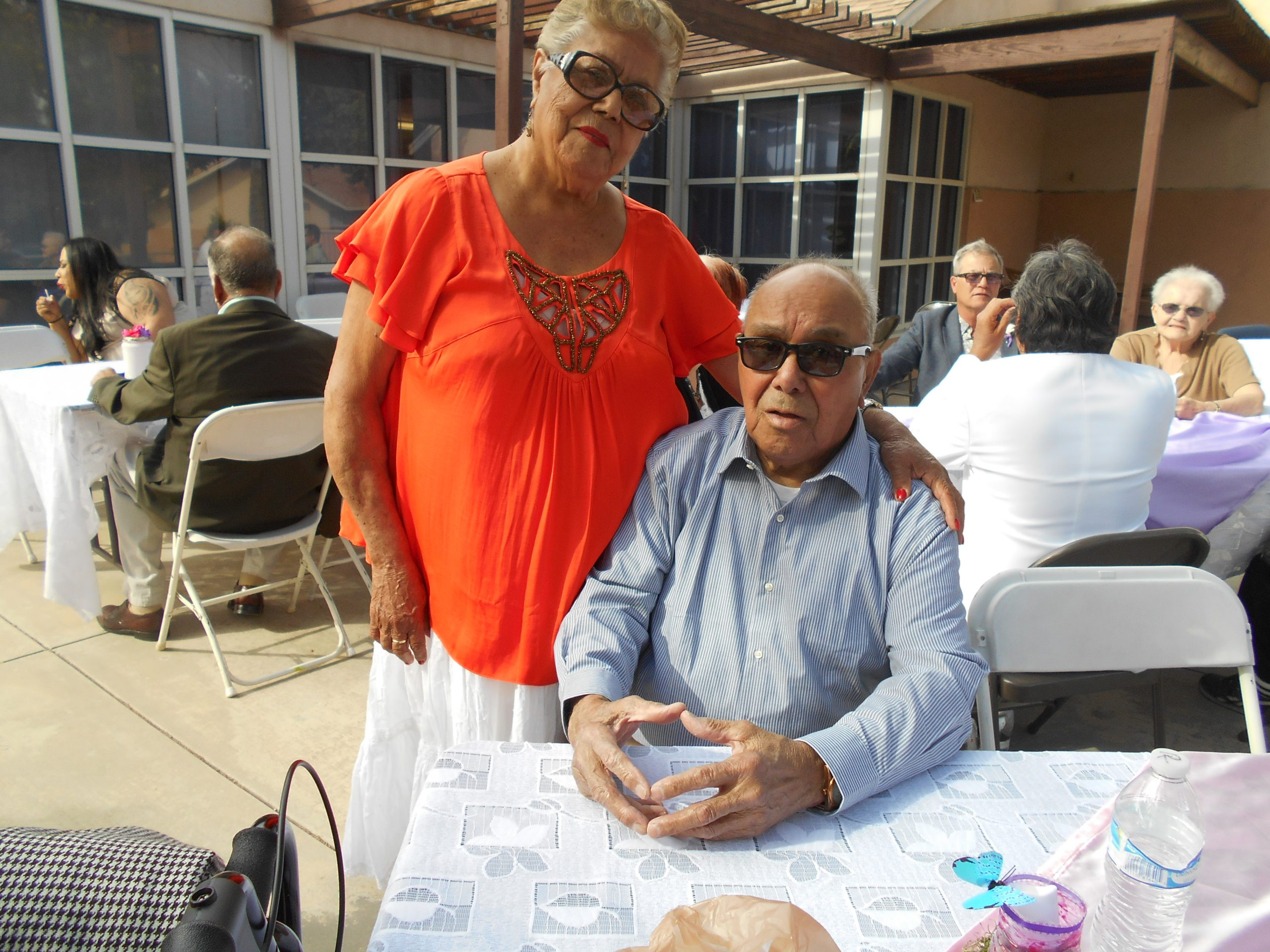 A man in a blue shirt and a woman in an orange shirt posing for a picture from behind a table at Cambridge Gardens senior housing community.