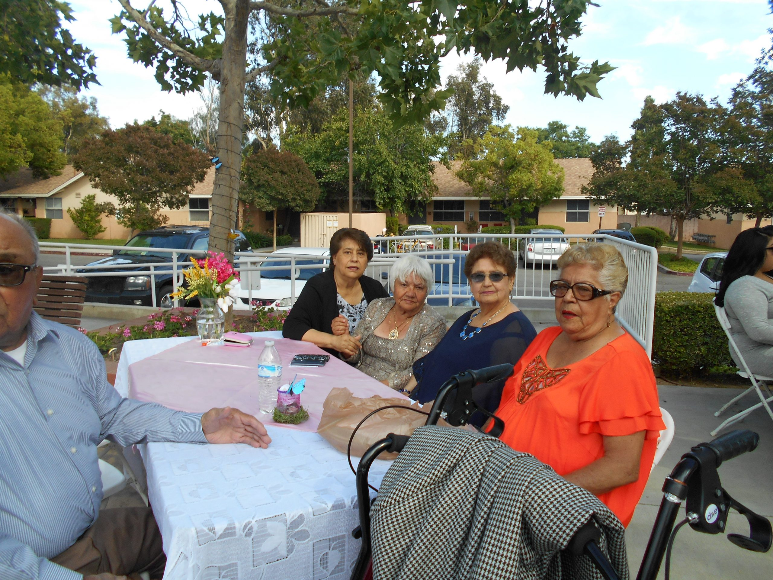 Photo of five residents, four women and one man, sitting outside at an event at Cambridge Gardens senior housing community.