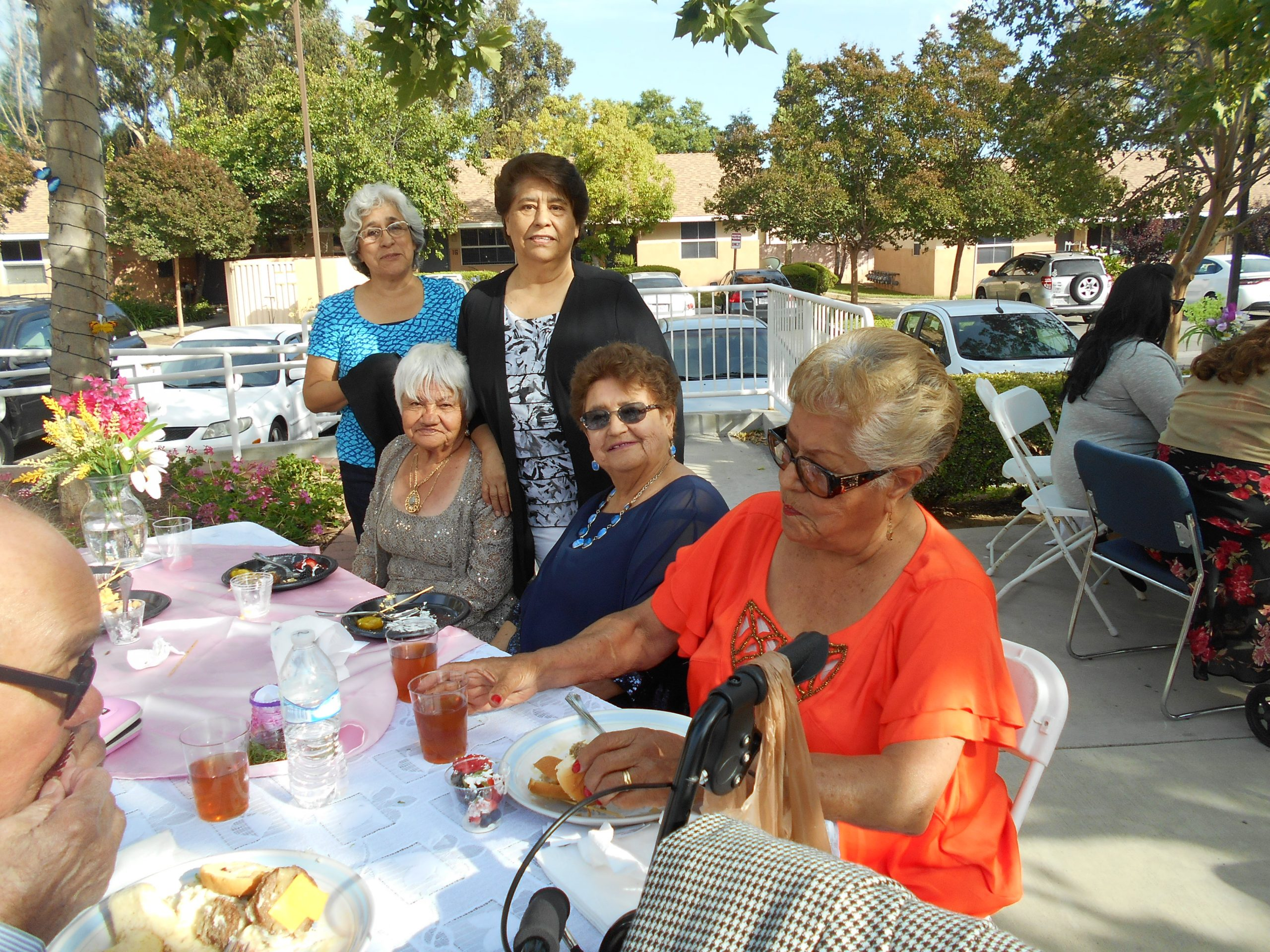 Photo of residents sitting outside at an event at Cambridge Gardens senior housing community.