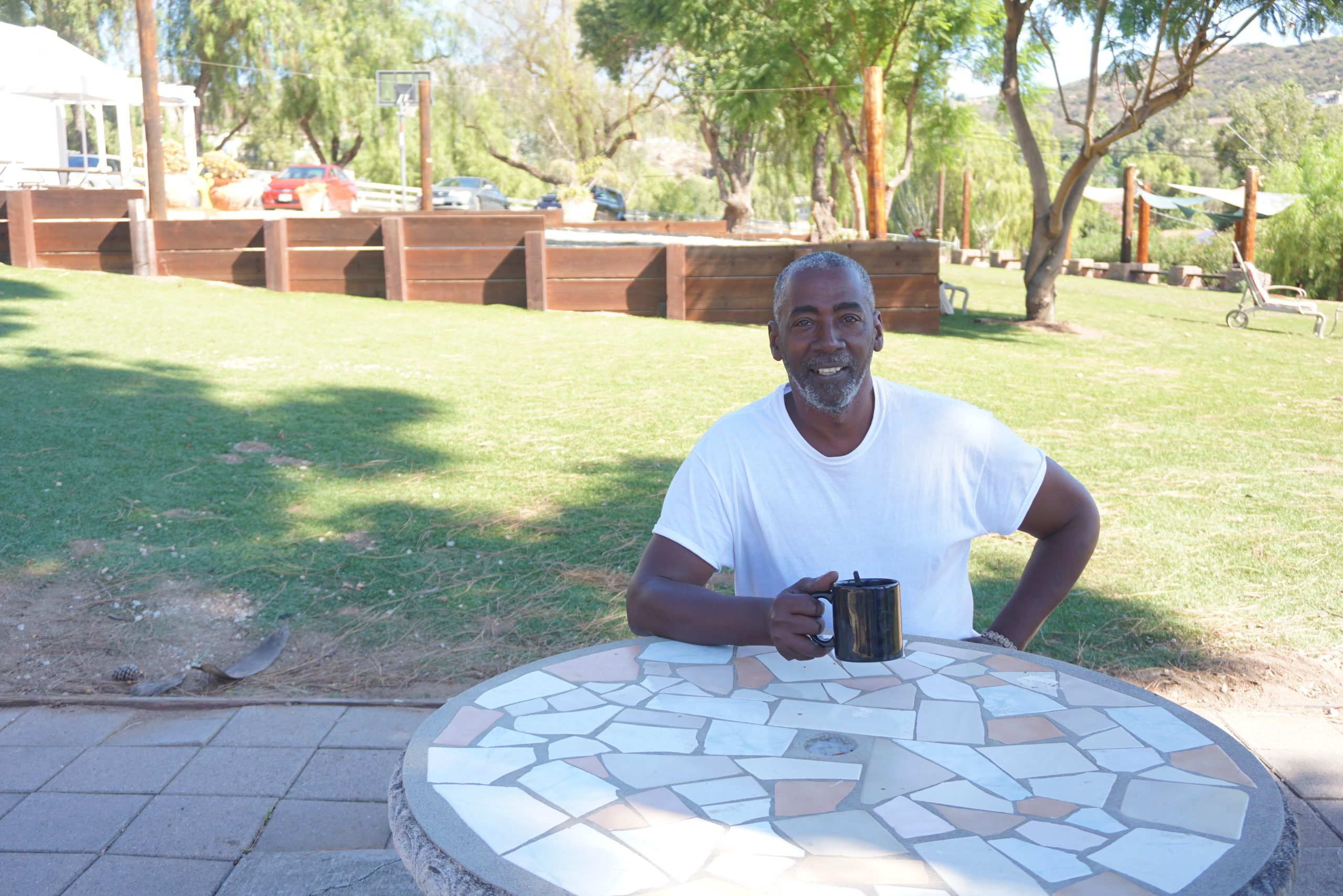 A man in a white shirt, sitting outside in the shade at a table smiling and holding a coffee cup. He is a part of what makes veteran housing communities important and successful.