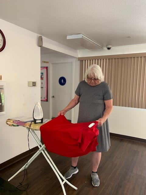 An older woman with white hair and glasses, wearing a grey dress ironing a red shirt on an ironing board at Cambridge Gardens senior housing community.