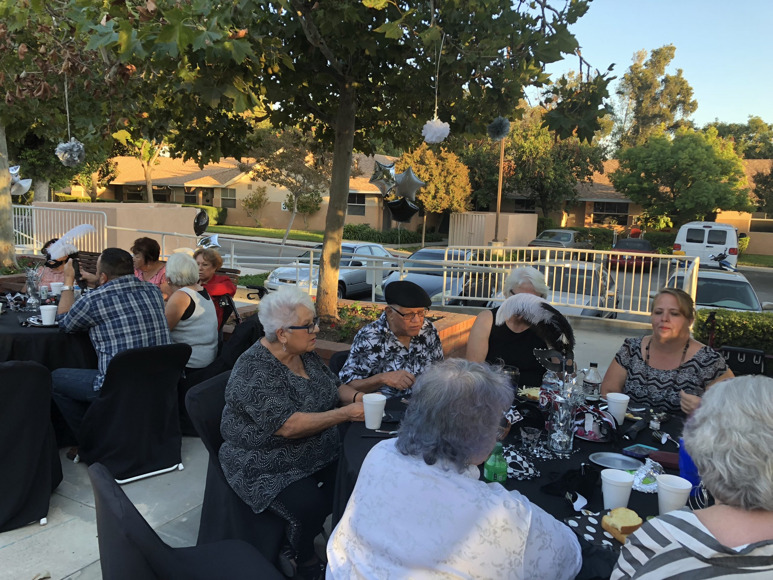 Photo of residents and family sitting outside at an event at Cambridge Gardens senior housing community.