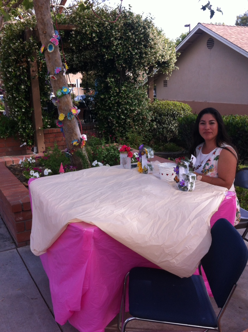A woman sitting at a table covered in pink fabric at the Cambridge Gardens senior housing community.