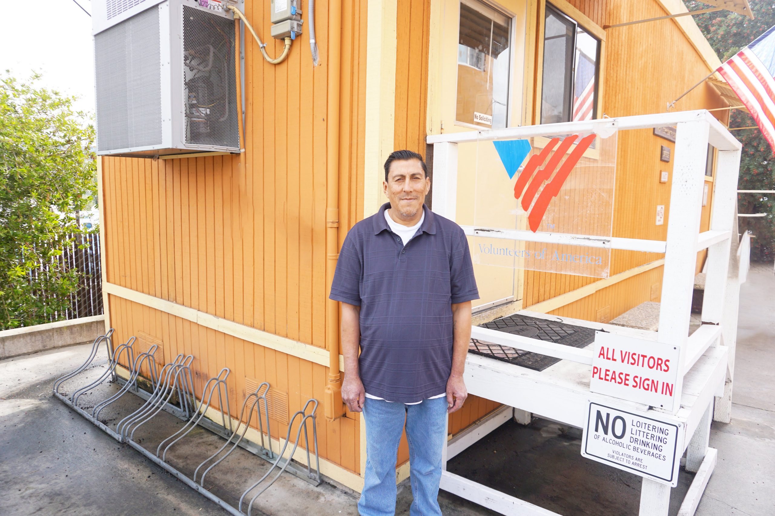 A man standing in front of a bright, orange-yellow building at the VOASW Troy Center for Supportive Living
