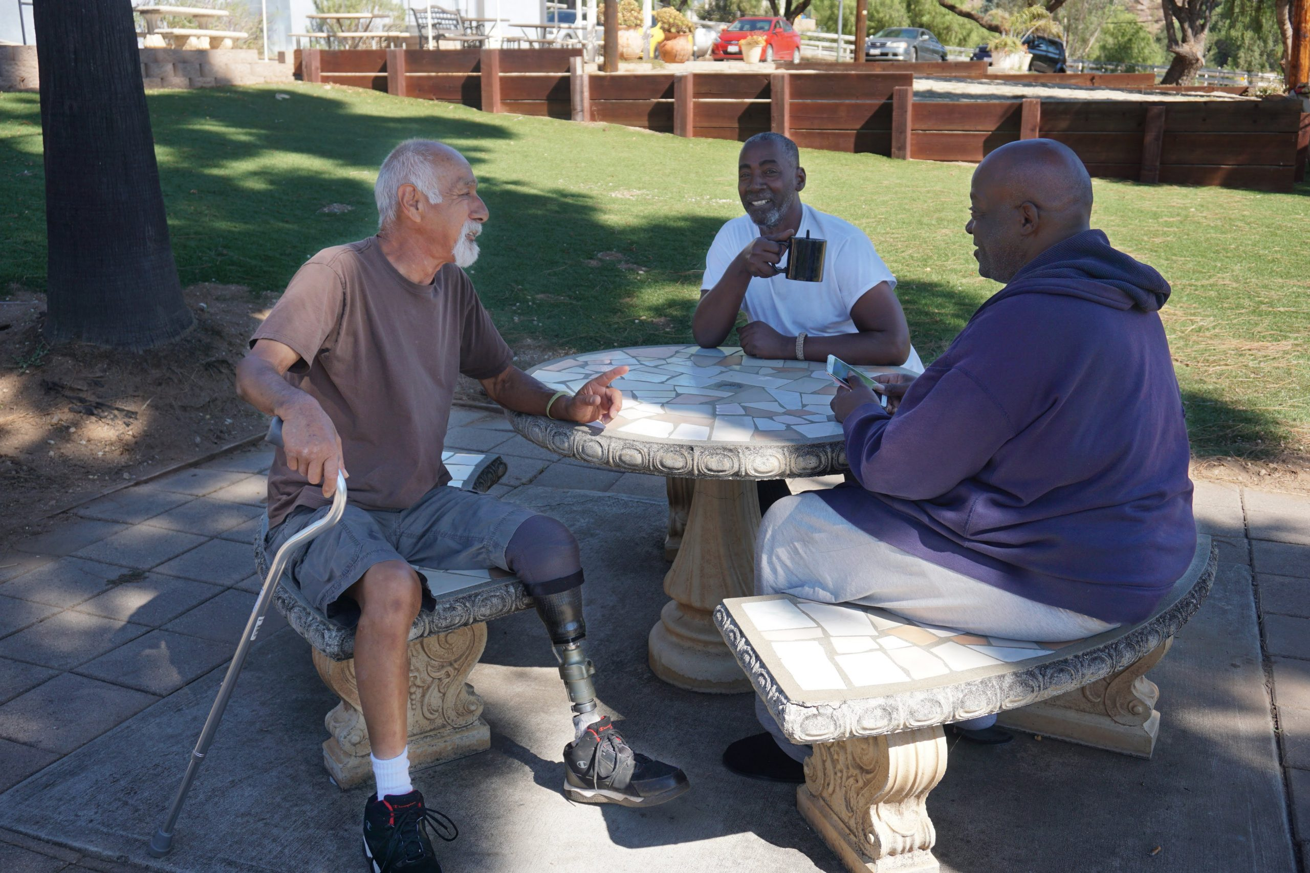 Three male veterans sitting outside at a Volunteers of America Southwest veteran housing community. Veteran housing communities provides both housing and services for veterans.