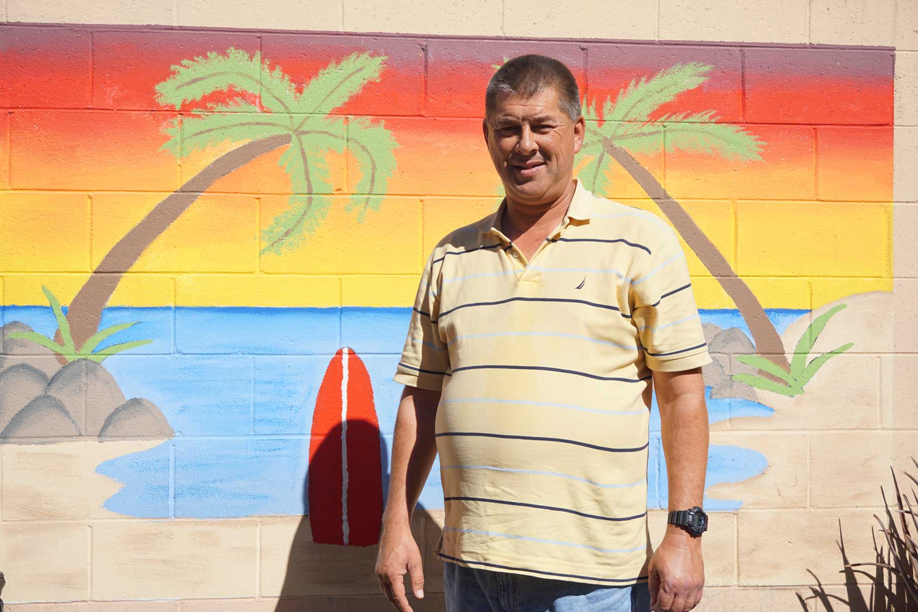 A man who is a suportive housing resident of the Luhman Center for Supportive Living adult residential care facility stands in front of a wall mural depicting a beach sunset, including sand, water, two palm trees and a red surfboard.
