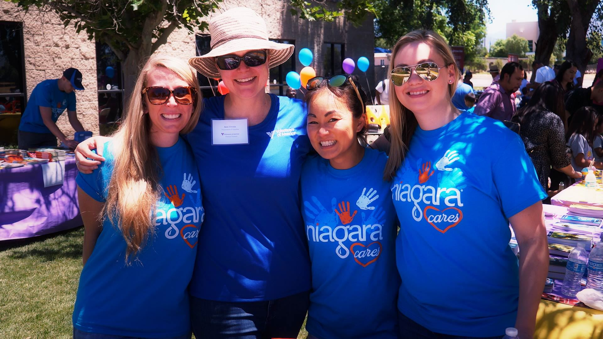 Photo of four women in blue t-shirts smiling and posing for a picture while performing nonprofit volunteer work.
