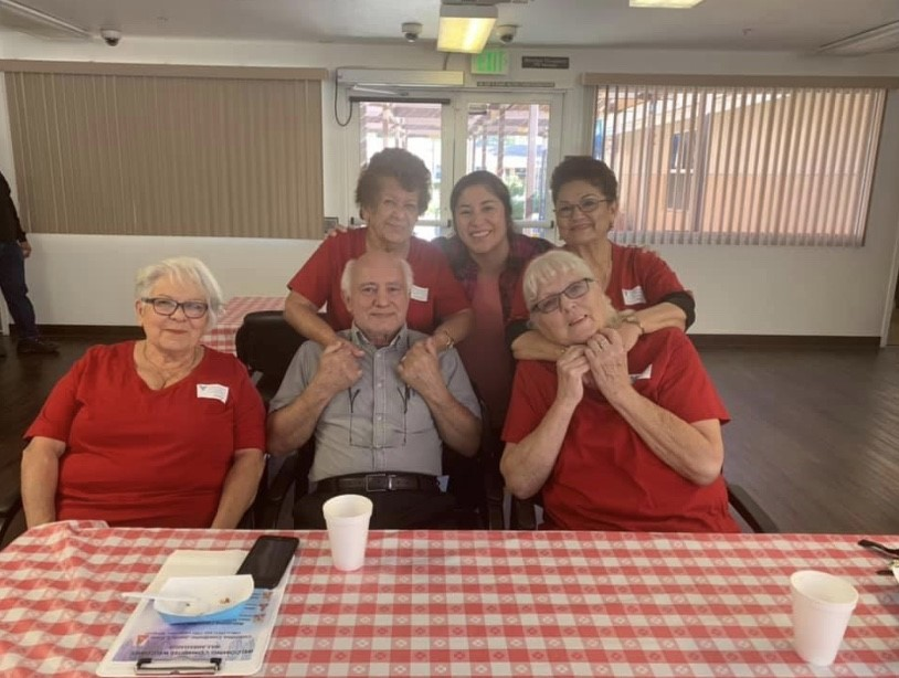 A group of seniors sitting inside at a table covered in the classic red and white checkered picnic pattern at Cambridge Gardens senior housing community.
