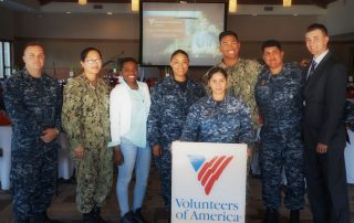 A photo of six people standing, five in military uniform, smiling and holding a VOASW banner, symbolic of Volunteers of America Southwest contact info.