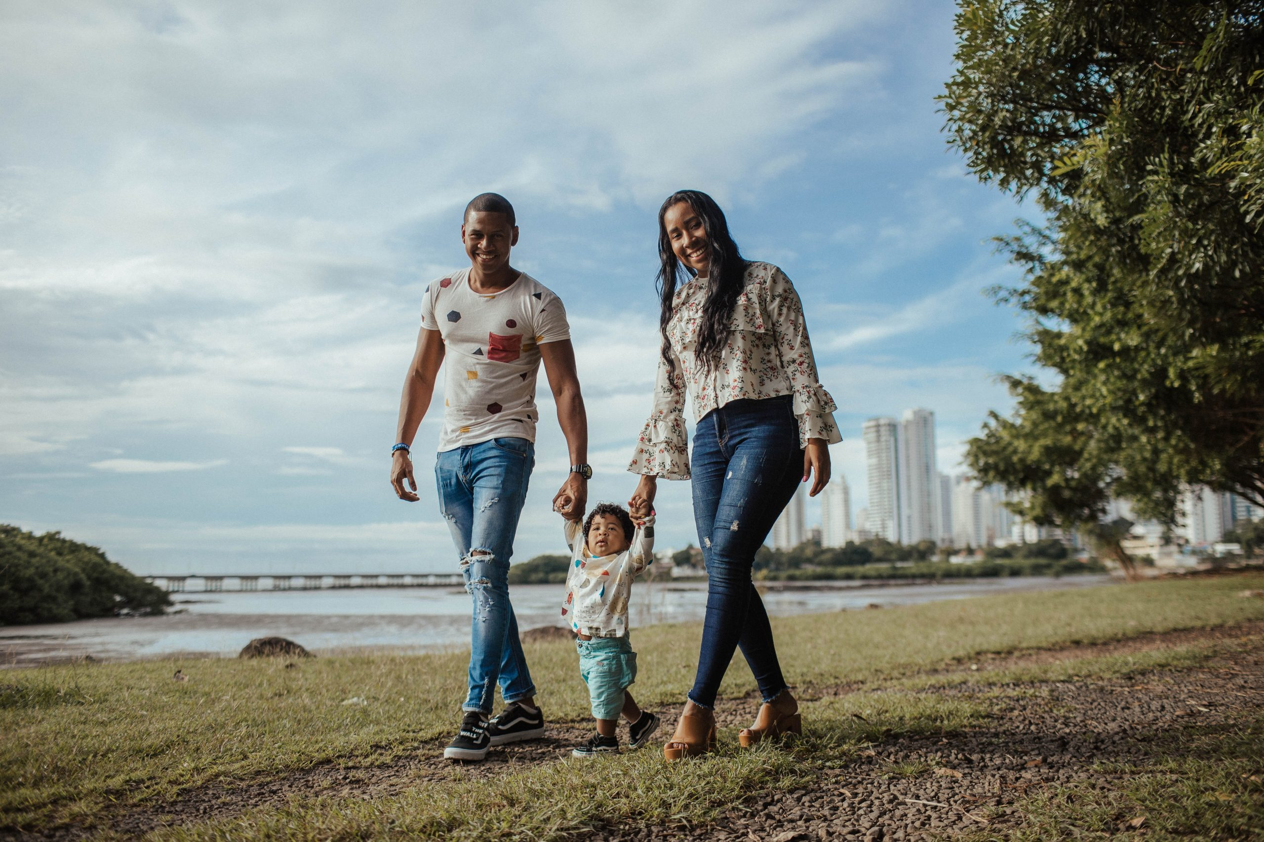 Photo of a man and woman parent couple walking through a park, each holding the hand of a toddler walking between them, symbolic of children and family services providerd by Volunteers of America Southwest.