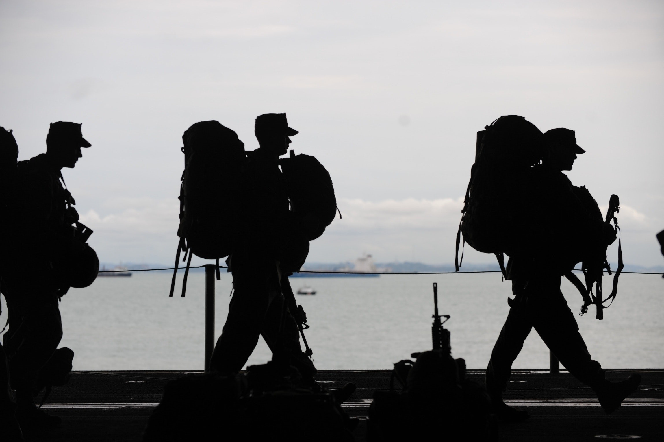 Three armed service members in shadow, carrying heavy equipment across a ship with an ocean and other ships in the background, symbolic of moral injury and women veterans.