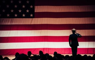 A uniformed man standing on a stage, facing and saluting a giant American flag that makes up the entire background. In the foreground there are men in the dark audience facing and saluting the American flag as a symbol of veterans assistance.
