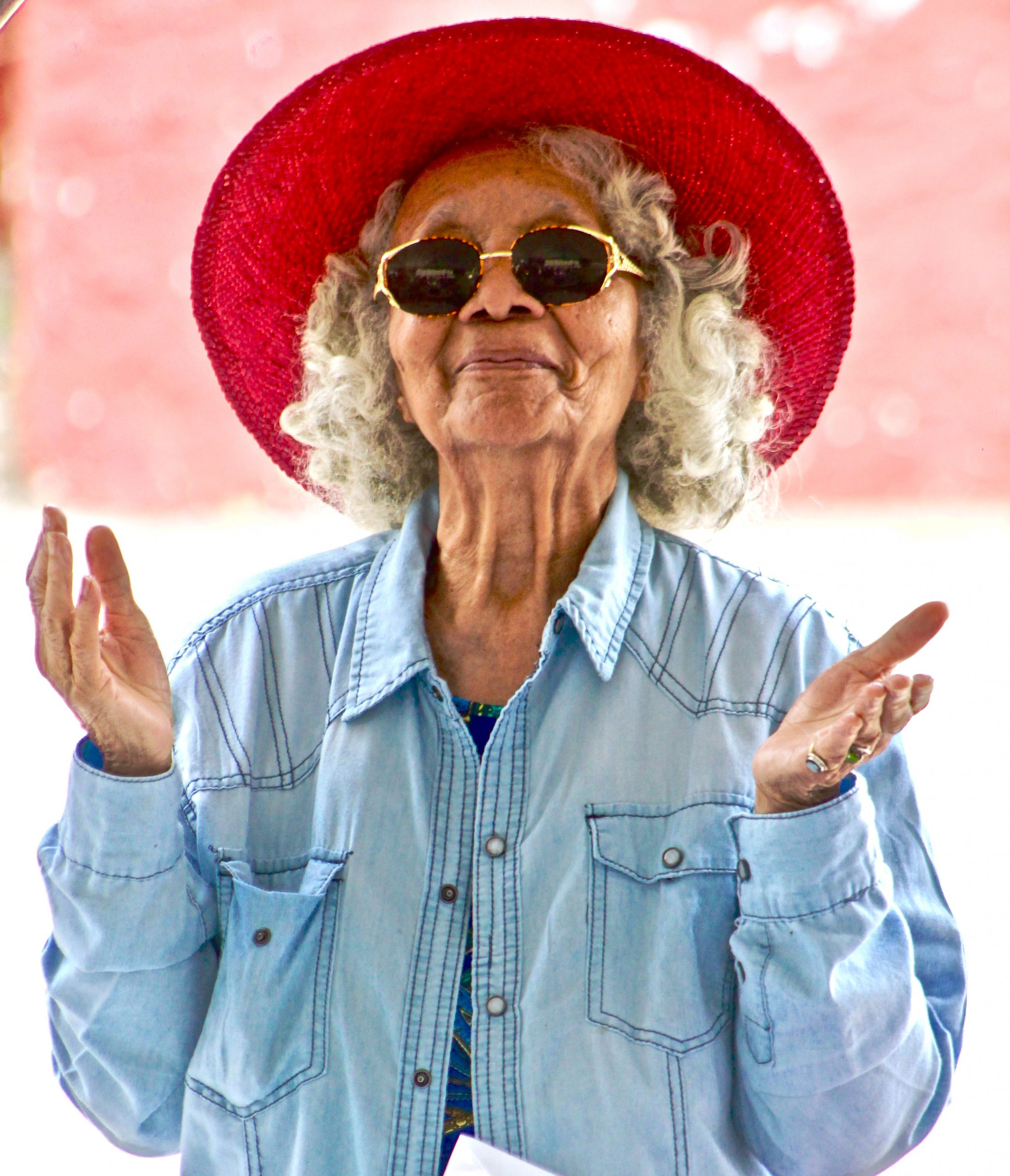 Senior woman with grey curly hair, wearing a blue denim jacket, sunglasses and red hat, smiling with raised hands symbolizing accessibility of food resources for seniors in San Diego.
