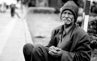 A black and white photo of an African-American man wearing a beanie, overcoat and pants while clasping is hands as he sits on a curb in the city. The image is meant to hightlight coronavirus among San Diego homeless population.