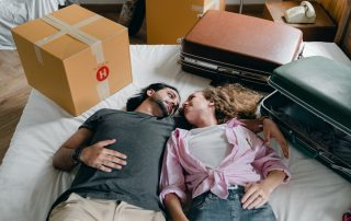 Photo of a couple laying on a bed and looking into each other's eyes, surrounded by packing boxes and two suitcases, meant to symbolize symbolizing the need for rental assistance in San Diego.