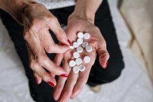 woman holding round white pills